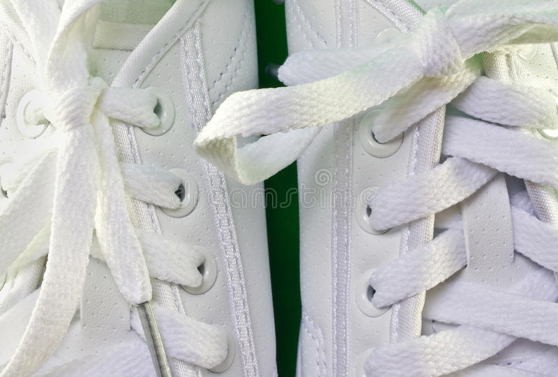 White tennis shoes. A closeup of white leather tennis shoes royalty free stock photography