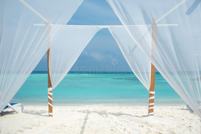 White tent for wedding ceremonies or romantic evening on a maldivian island. Beautiful view with white sand and blue sea royalty free stock photo