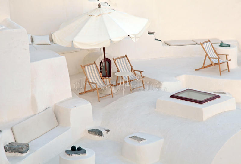 White terrace with deck chairs in caldera house, Santorini, Gree stock photography