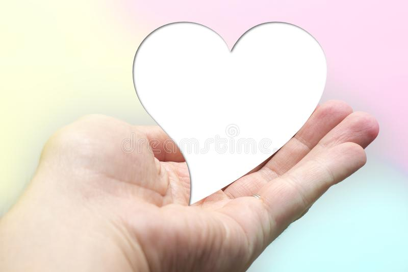 White for text heart shape lay on hand with colorful background. stock photography