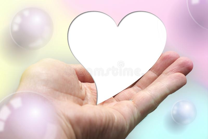 White for text heart shape lay on hand with colorful background. Valentine day. Yellow pink aqua blur royalty free stock photography