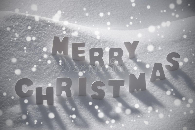 White Text Merry Christmas On Snow, Snowflakes. White Wooden Letters Building English Word Merry Christmas. Snow And Snowy Scenery With Snowfalkes. Christmas royalty free stock photo