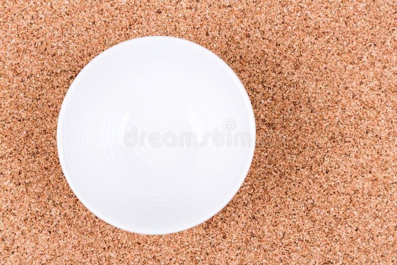 White textured bowl on a plain cork background stock photo