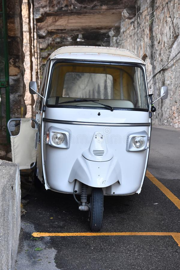 White three wheeled car in th narrow streets of Scilla, Calabria. Three wheeled car in an alleyway in the ancient village of Sculla o in Calabria, southern Italy royalty free stock image