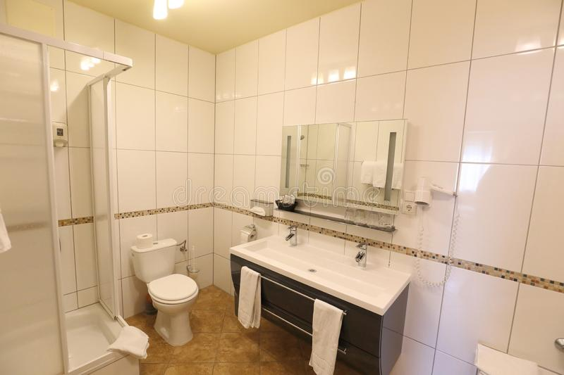White tiled bathroom with shower corner and toilet royalty free stock image