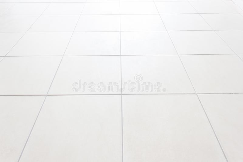 White Tiles floor texture.White tile floor office With the morning sun, the windows reflect the reflection. royalty free stock photography