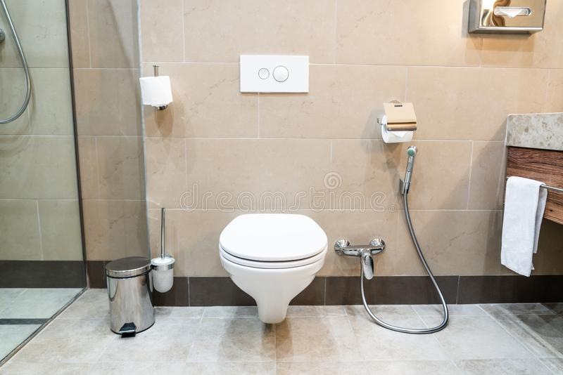 White toilet bowl in a modern bathroom with shower royalty free stock photography