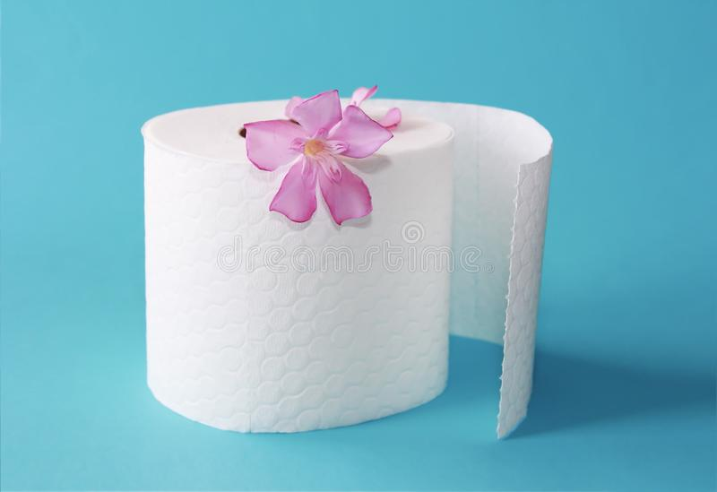 White toilet paper roll with flowers decor on a blue background stock image