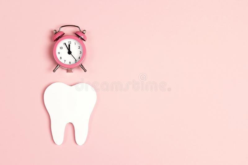 White tooth with alarm clock on pink background. Time to dental health. Dentist day concept. Flat lay, top view, copy space for text royalty free stock photography