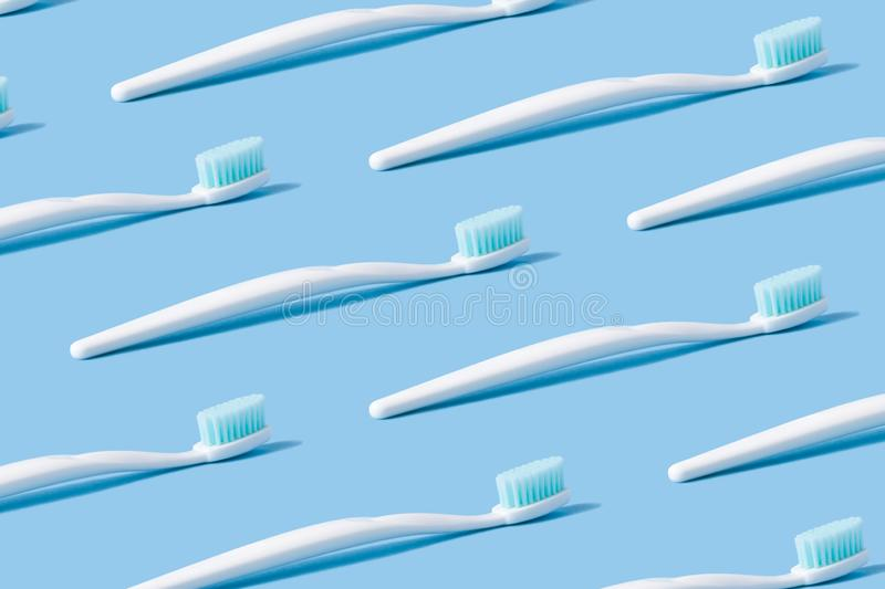 A collage of white toothbrushes on a blue paper background. stock images