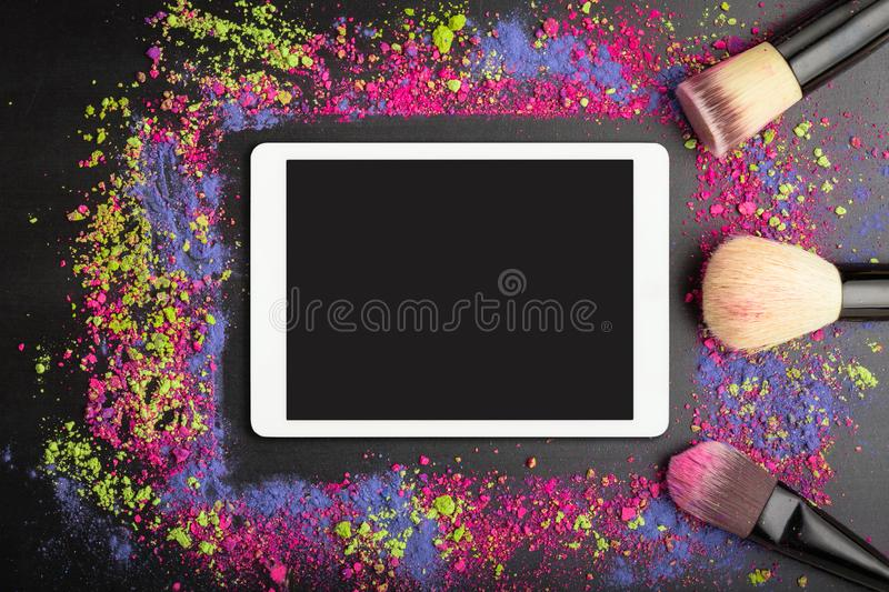 White touchpad with blank touchscreen with professional makeup brushes on colorful background of crumbled eyeshadows royalty free stock images