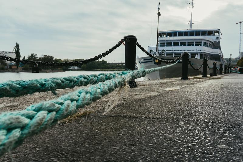 White tourist liner at the wharf tied with a rope stock image