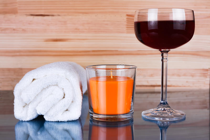 White towel, orange candle and a glass of wine. royalty free stock image
