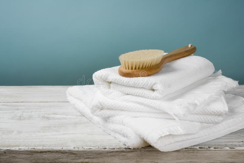 White towels and bath brush on wood over blue background stock images