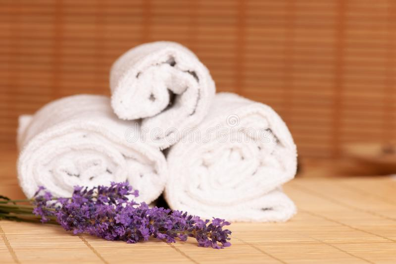 White towels and massage rocks in spa salon over dark and light royalty free stock photo