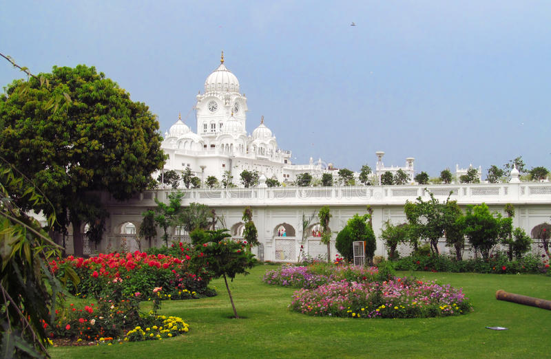 White towers near Golden Temple Amritsar, India. White towers and garden with flowers near Harmandir Sahib - Golden Temple, in Amritsar, India. The holy place of royalty free stock photo