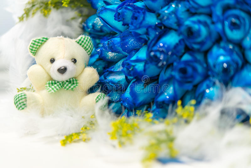 Bear and flower. A white toy bear and many blue roses stock photo