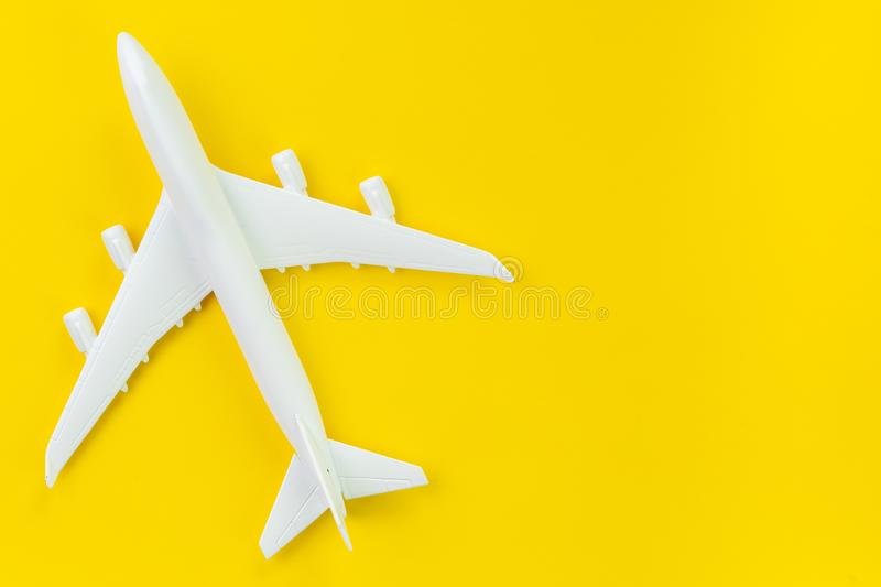 White toy commercial airplane on solid yellow background using as travel and transportation business wallpaper.  royalty free stock image