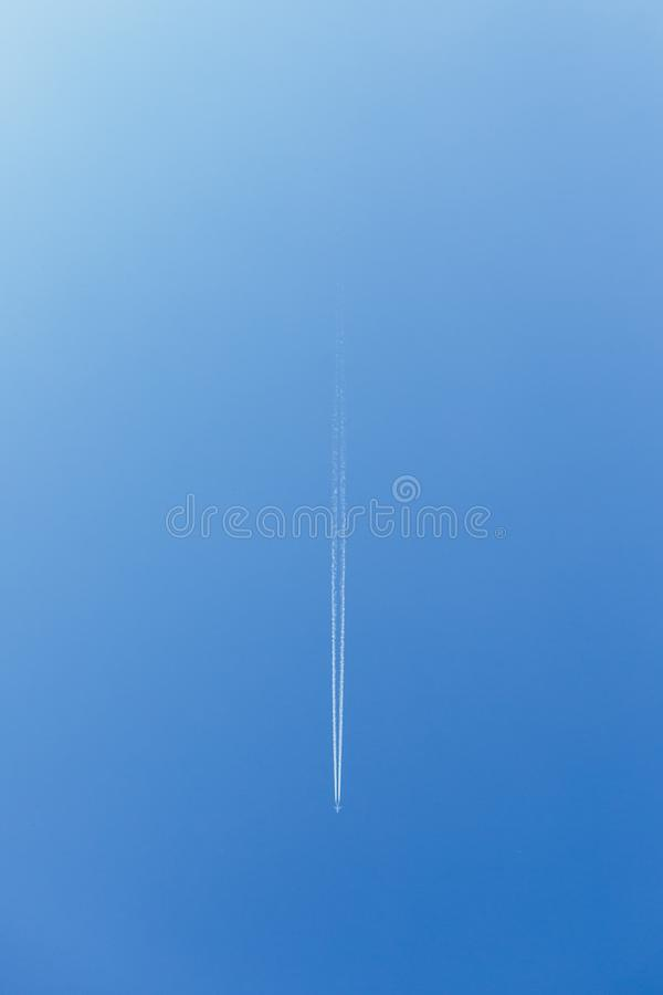 White trace of smoke from flying airplane. Vertical image. Plane flying in blue sky and living white track line smoke. Aircraft royalty free stock image