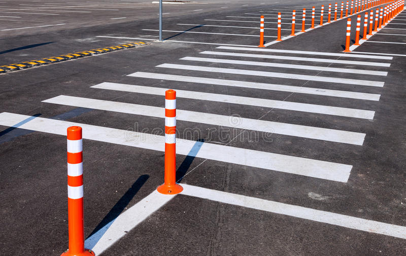 White traffic markings with a pedestrian crossing. On a gray asphalt parking lot stock photo