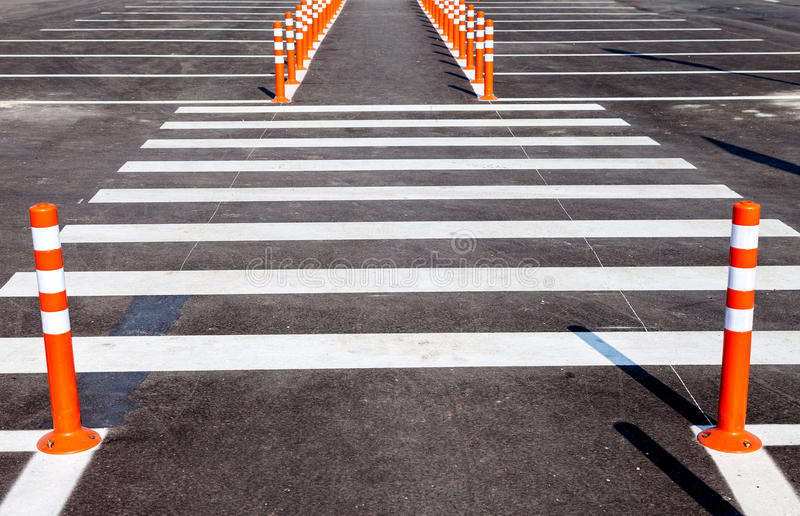 White traffic markings with a pedestrian crossing. On a gray asphalt parking lot stock photos