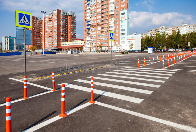 White traffic markings with a pedestrian crossing. On a gray asphalt parking lot stock photography