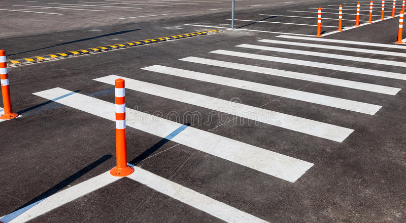White traffic markings with a pedestrian crossing. On a gray asphalt parking lot royalty free stock image