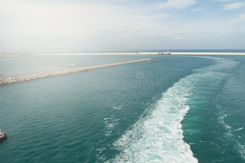 White trail, foam and waves on the Mediterranean sea behind the liner sailing from the port of Valencia, view of the port,. Lighthouse, breakwater, travel royalty free stock image