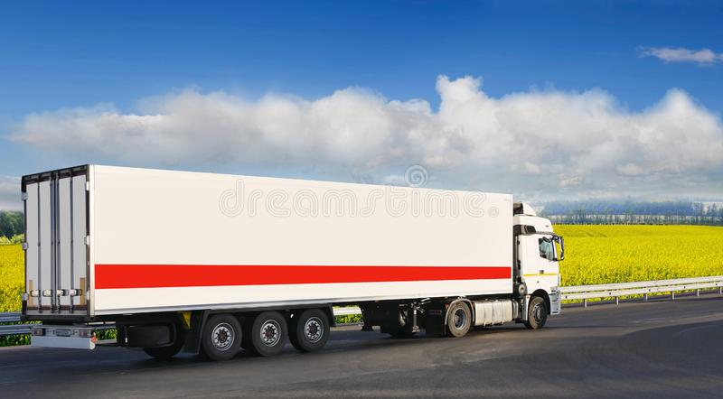 White trailer on the highway, against the background of a green field stock images