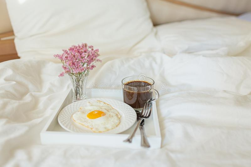 White tray with breakfast on a bed in a hotel room. Fried egg, cup of coffee and flowers in white sheets in light bedroom royalty free stock photography