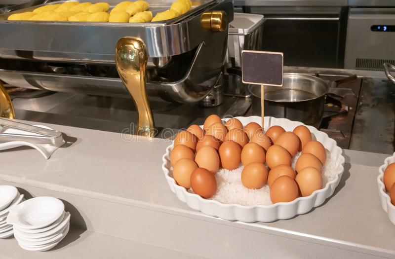 A white tray filled with boiled egg on salt crystal at omelet stataion for breakfast. Detail of buffet line stock photography