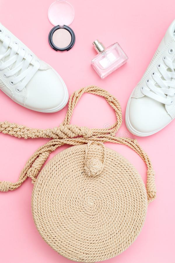 White trendy sneakers  and feminine accessories on pink pastel background. Front view stock images
