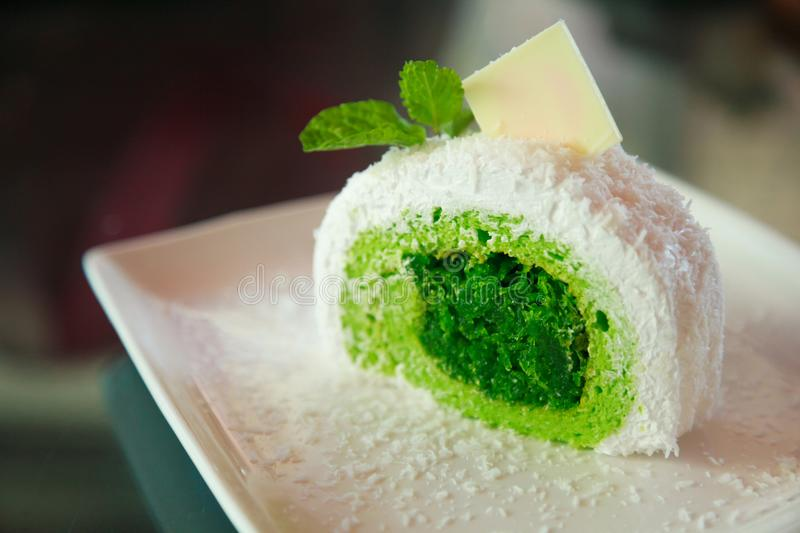 White tropical coconut cake with green pandan flavor on shredded coconut filling, topped mint leaves and white chocolate stock photo