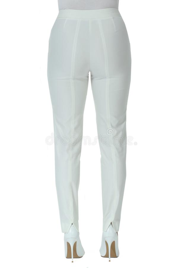 White trousers on model legs with white stiletto heels shoes. Isolated on white royalty free stock photo