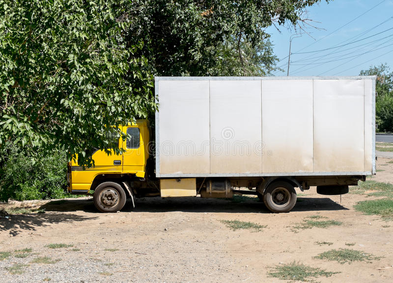 White truch parked near tree side view royalty free stock image