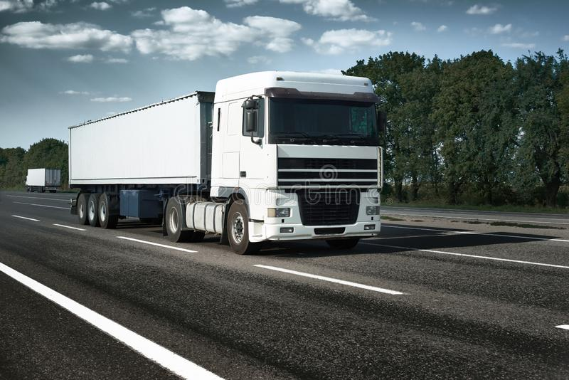 White truck is going up the road. Cargo transportation concept stock images