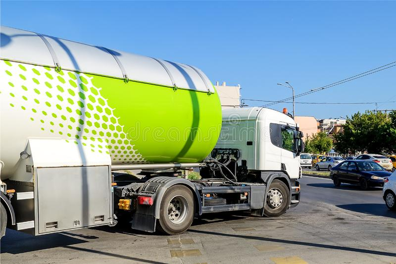 White truck with a tank for propane or other fuel transportation turns on the main road in the city on a sunny day stock photos