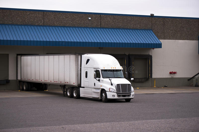 White truck with a trailer in a warehouse on the unloading. White modern truck complete with a trailer is unloaded at the dock on the warehouse with a number of stock photo