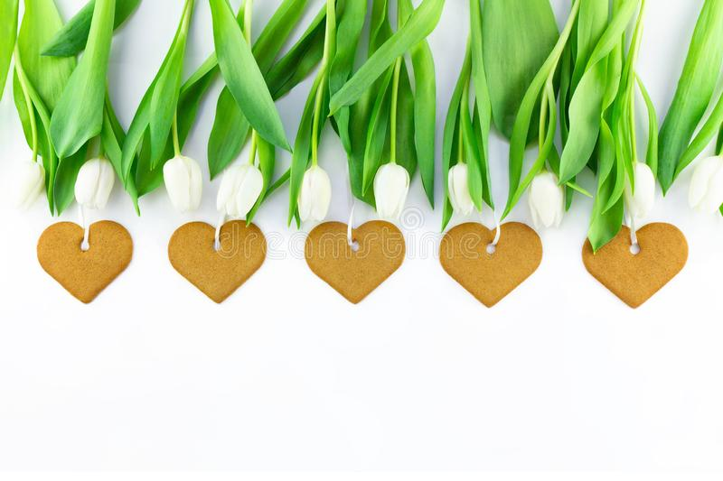 White tulips and heart shaped cookies on white background with copy space. Spring, Mother`s day or Easter concept stock image
