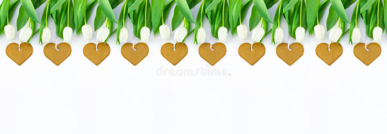 White tulips and heart shaped cookies on white background with copy space. Top view, banner for website stock photo