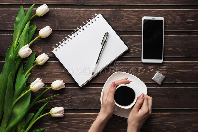 White tulips on a wooden table with an empty notebook and smartphone and a Cup of coffee in women`s hands. Flat lay, top view composition with copy space stock image