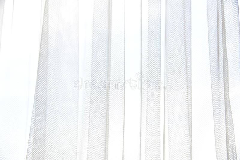 White tulle curtain with vertical folds. Window with light curtains. Soft textile texture. Light and shadow abstract stock photos