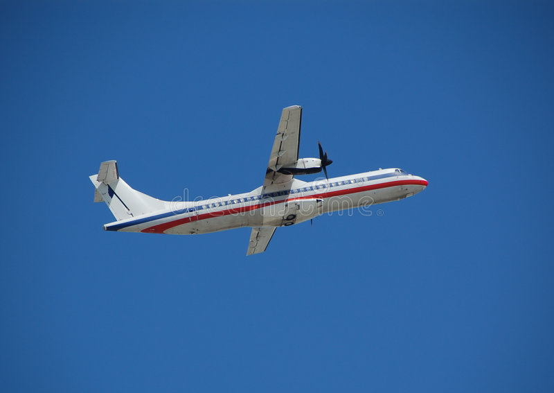 White turboprop airplane taking off against blue sky royalty free stock image
