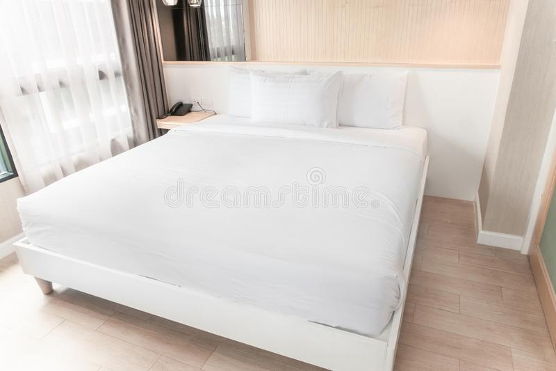 The white twin bed is set in a wood and pastel decorated stock photos