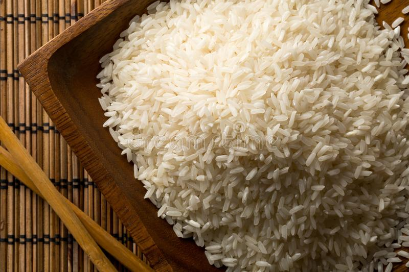 White uncooked, raw long grain rice in wooden bowl with chopsticks on bamboo mat top view flat lay from above royalty free stock photography
