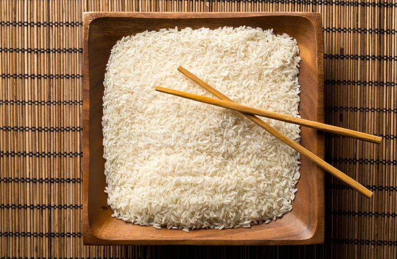 White uncooked, raw long grain rice on wooden plate with chopsticks on bamboo mat with copy space top view flat lay from above royalty free stock images