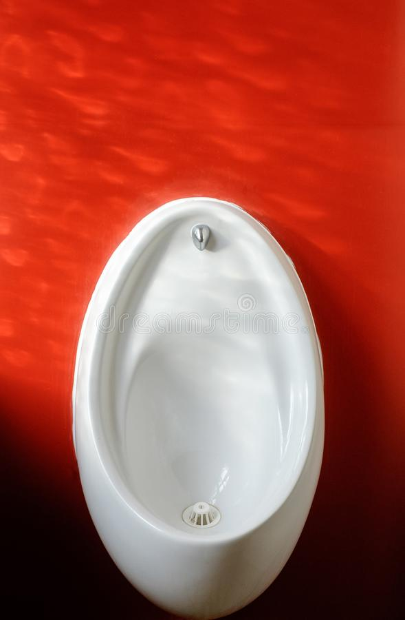 Free White Urinal Basin Against Red Wall Royalty Free Stock Photos - 140195588