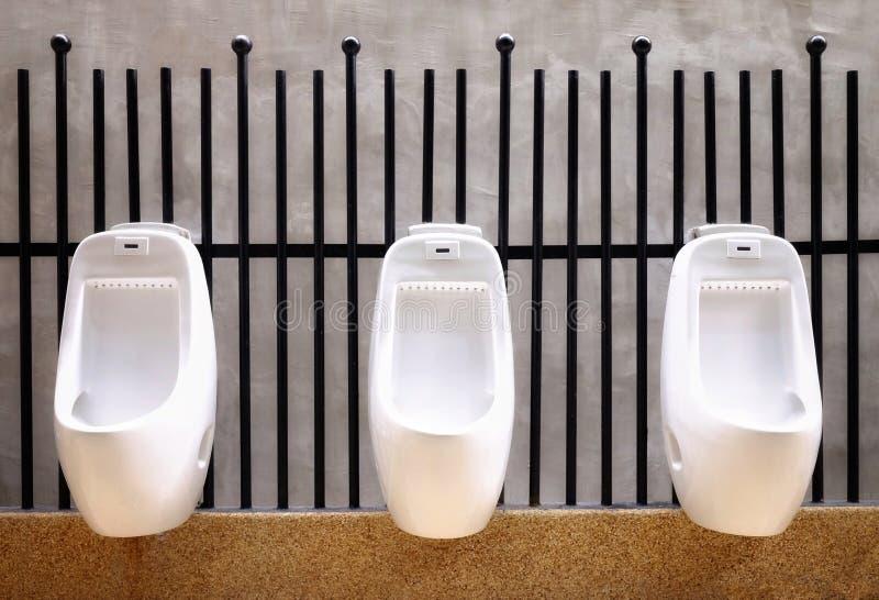 White urine hanging on the black steel / Outdoor restroom / men toilet / stock image
