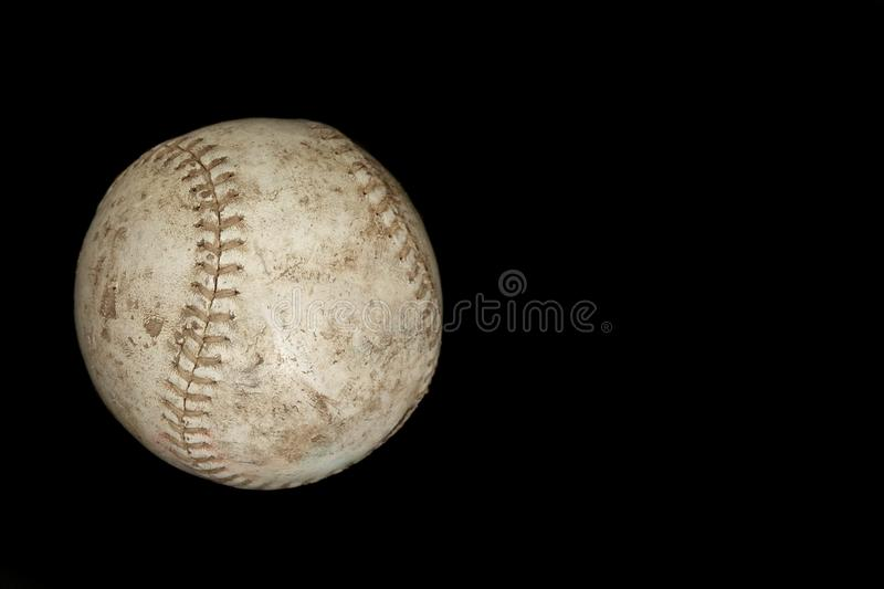 White Used Softball Set Against a Solid Black Background with Copyspace. A white, used, and well-worn softball is set against a solid, black background with royalty free stock photo