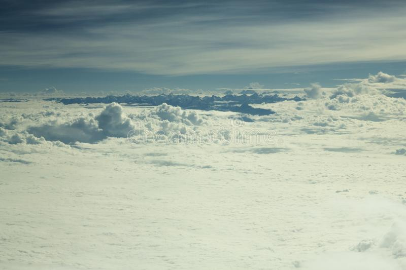 A white valley of clouds under the blue sky and protruding black tops of high mountains. White valley of clouds under the blue sky and protruding black tops of stock photography